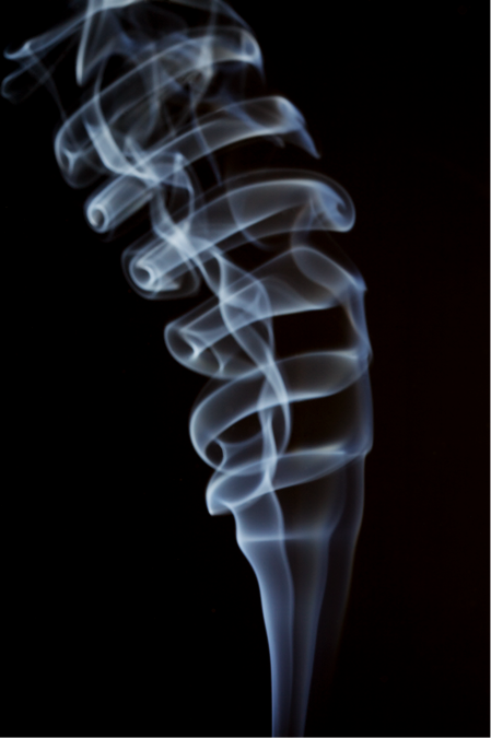 The complex curl of smoke from a stick of incense, frozen by a burst of flash from a 580EX II.